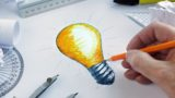 Designer drawing a light bulb, concept for brainstorming